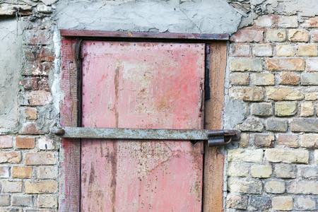 eyesore: metal door in garage brick wall background Stock Photo