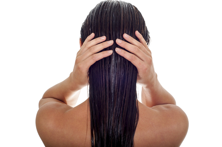 moisturizers: Hair care concept. Back view of woman with long wet hair, white background