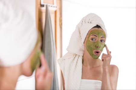 The woman applies green organic face mask in the bathroom