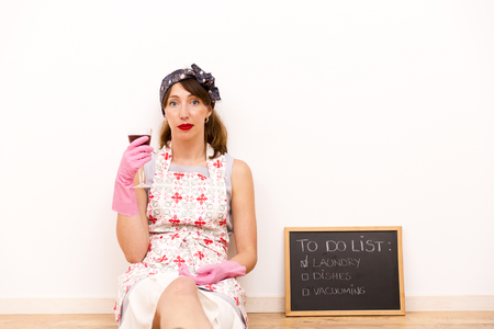 doing chores: Housewife with black chalkboard with a to do list and glass of wine in hand Stock Photo