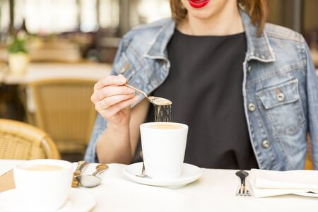 Beautiful young girl resting in a cafe, adding sugar into coffee