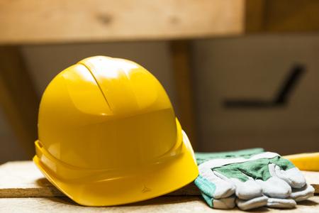 Casco de seguridad amarillo y guantes en la superficie de trabajo en el sitio de renovación del ático