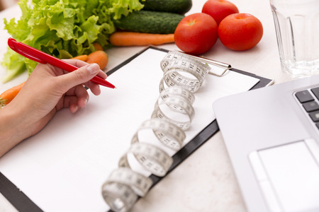dietology: Healthy lifestyle concept. Writing weight loss plan with fresh vegetable diet and fitness Stock Photo