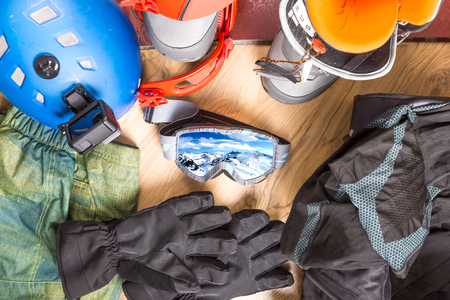 Getting ready for winter vacation. Set of snowboard equipment on the wooden floor. Goggles, snowboard, jacket, boots, gloves, suitcase