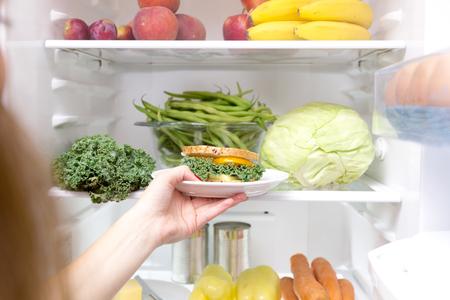 冷蔵庫のヘルシーなサンドイッチを取る女性