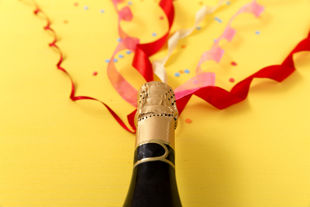 Colorful ribbons popping out of champagne bottle