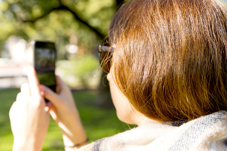 Young woman using mobile phone to take photo outdoors at the park