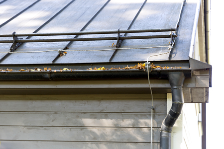 Rain gutter pipeline system installation. Roofing construction. Rain gutter system and roof protection from snow (Snow guard)