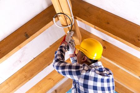 Electrician working with wires at attic renovation site Zdjęcie Seryjne