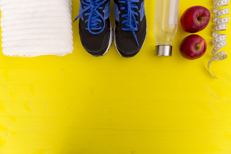 Fitness equipment. Healthy food. Sneakers, water,apple, measuring tape on yellow wooden background