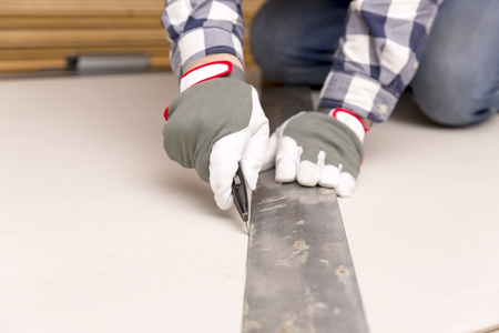 worker cutting plasterboard with construction knife. Attic renovation Stock Photo