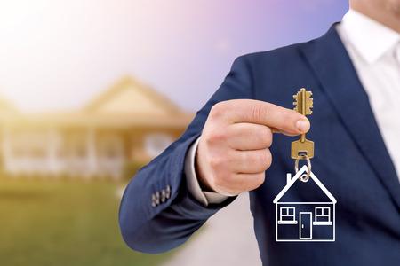 Agent nieruchomości trzyma klucze przed pięknym nowym domem. Zdjęcie Seryjne