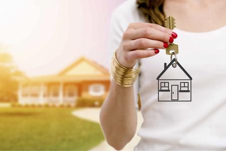 investment real state: Agente inmobiliario que sostiene llaves delante de una nueva casa hermosa.