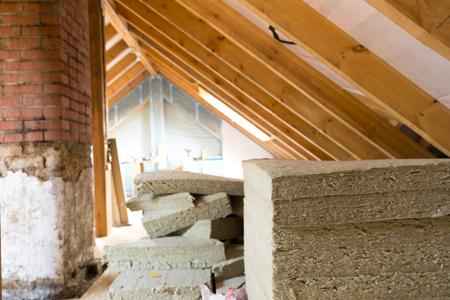 View of attic renovation and construction site with pile of rockwool prepared to be installed