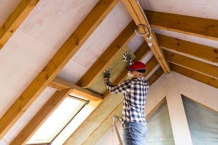 Mann, der thermische Dachisolierungsschicht - unter Verwendung der Mineralwolleplatten installiert. Dachgeschoss Renovierung und Isolierung Konzept