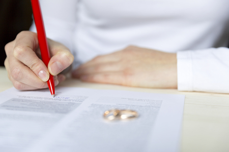 Women signs divorce papers and takes of the ring Stock Photo