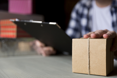 Delivery man checking package according to description on chalckboard