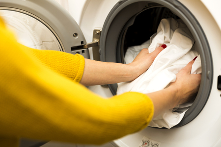 Woman hand loading dirty clothes in washing machine