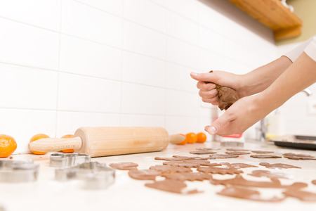 Making gingerbread cookies for Christmas in kitchen. Womans hands, dough roll, gingerbread cutter, tangerines