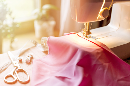 Tailoring Process - Womens hands behind her sewing machine Stock Photo