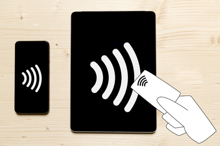 Contactless payment icon on cell phone, tablet and down credit card in hand. Tap to pay concept - vector sign 版權商用圖片