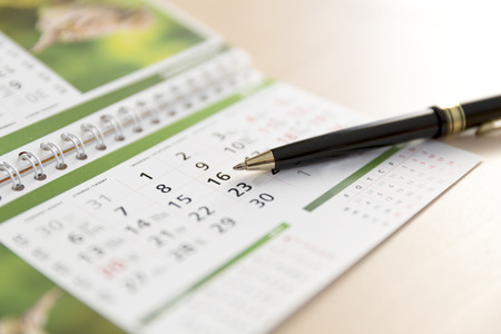 An Image of a calendar and a pen