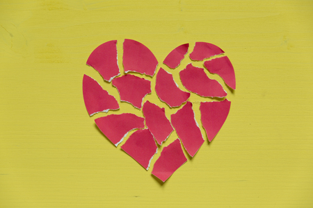 Crushed paper heart on yellow background. Broken heart concept