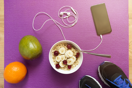 Oatmeal with fruits after a workout . Fitness and healthy lifestyle concept. Bowl of oatmeal, orange, mango, smartphone and sneakers Stock Photo