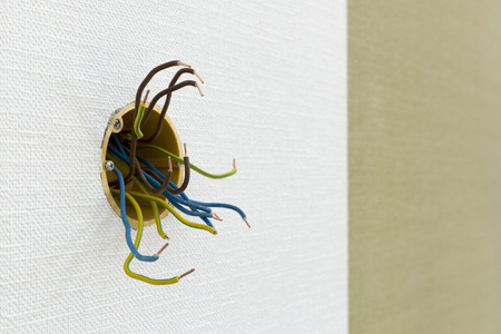 Several exposed electrical copper wires protruding from a whitewall. 写真素材