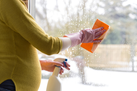 Pregnant woman cleaning window with cloth and window spray. Sping cleaning concept