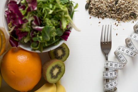 Healthy fruit,vegetables and measuring tape around the fork. Weight loss and right nutrition concept