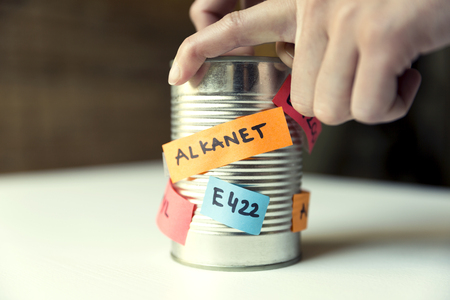 Womans hand opening canned food with paper notes naming food additives. Healthy food concept