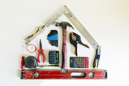 Home renovation concept. Shape of a house from construction tools. Stock Photo
