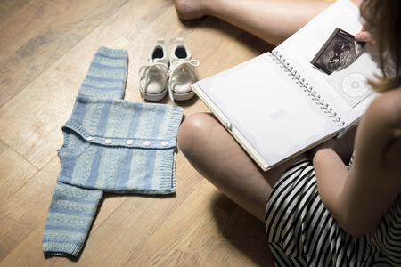 Woman placing babys sonogram into babys first year memory book. Baby clothes and sneakers laying on the floor Stock Photo
