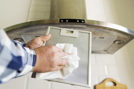 Mani dell'uomo che puliscono filtro a rete in alluminio per cappa da cucina. Lavori domestici e faccende domestiche. Cucina cappa sullo sfondo