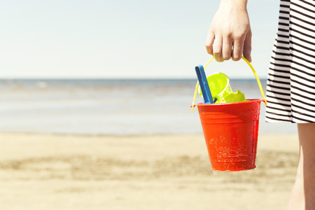 Woman holding bucket with children's beach toys - spade and shovel on a sunny day