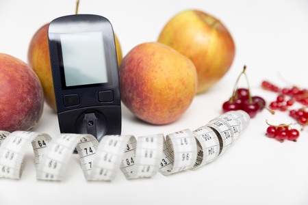 Diabetes monitor, diet and healthy food eating nutritional concept with clean fruits with diabetic measuring tool kit ans measuring tape Banque d'images