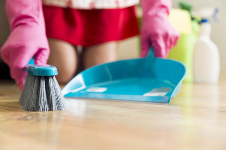 Housework, cleaning and housekeeping concept - woman with brush and dustpan sweeping floor at home
