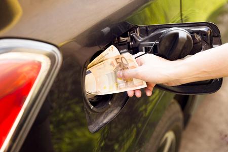 Transportation expenses concept - Euro money in car fuel tank Zdjęcie Seryjne