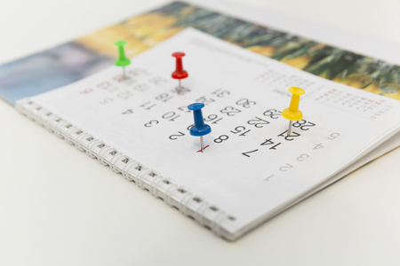 Colorful pins push marking on a calendar. Busy schedule