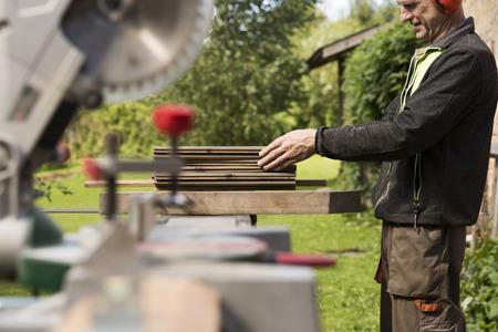 Senior men preparing wood materials with rotary saw