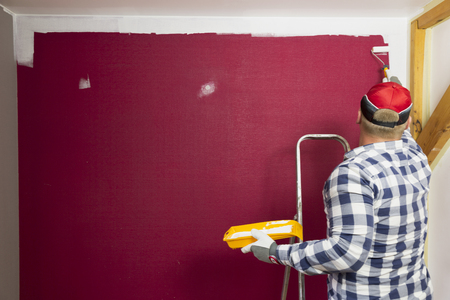Home improvement. A man in a red hat coloring a room with a paint roller and paint brush.