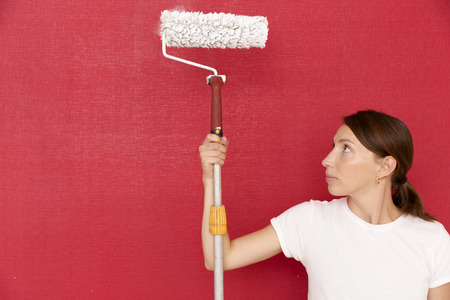 Home improvement. Beautiful woman painting wall with paint roller.