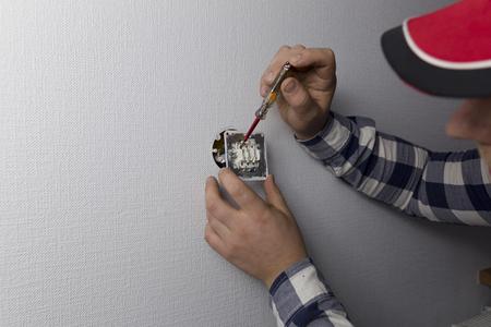 Un elettricista viene controllato con un indicatore o l'interruttore della luce è alimentato