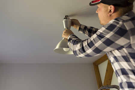 The electrician installs the ceiling lamp Imagens
