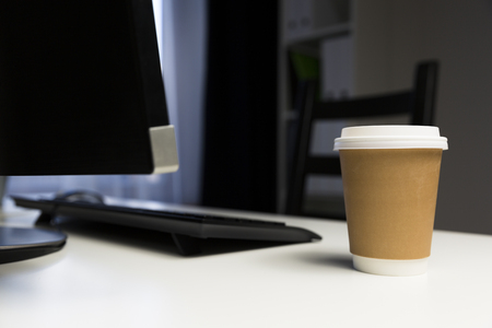 Cup of coffee in office next to computter. Working late concept Фото со стока