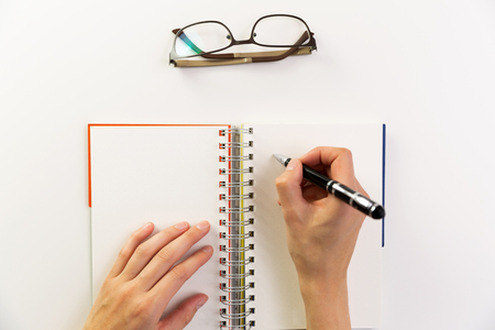Womans hands with pen writing on notebook. Modern office desk. Working, writing concept Stock Photo