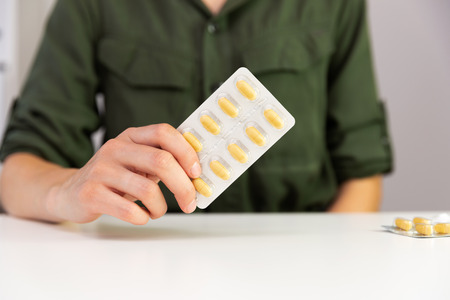 Womans hand holding package of pills, medicine, vitamins and drugs. Stock Photo