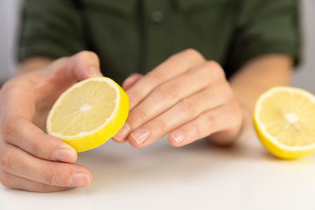 Manicure, woman cleans her nails with lemon.