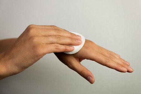 Women cleaning hands with cotton pad